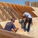 Workers putting down roof sheathing. Tarpaper and shingles go over this. Picture from this website.